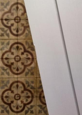 Details of a wooden door being painted light grey