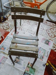 old metal chair after two coats of paint stripper