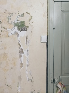 cracked plaster and damaged paint in our tiny kitchen